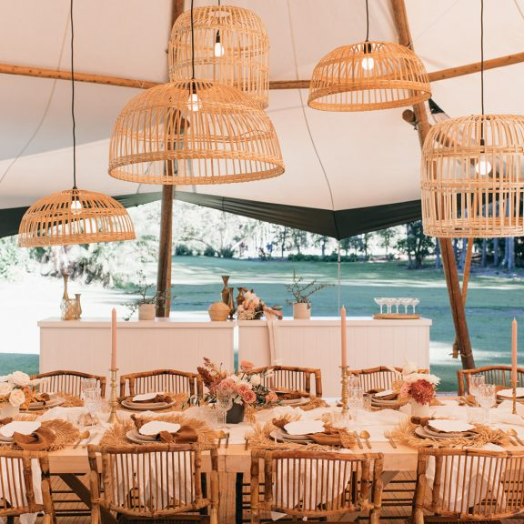 A table setting for a tipi wedding at The Acre featuring beautiful hanging installations and flowers.