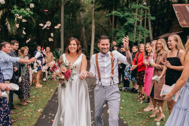 A bride and groom walk down the ailse at their outdoor wedding at The Acre. Guests throw confetti.