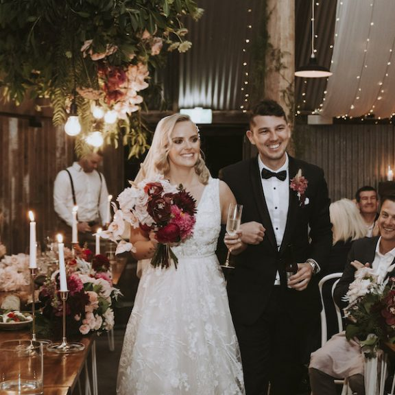 A bride and groom inside the barn at The Acre. The bride holds red flowers. There are fairy lights on the roof.