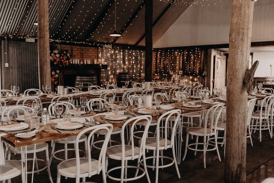Wedding reception barn with tables and chairs  set up and fairy lights