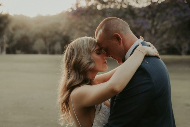 A bride and groom rest their foreheads against each other.