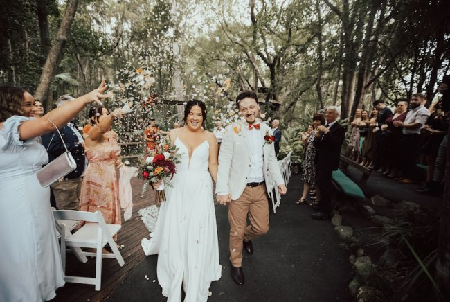 Guests throw confetti over a bride and groom. There are huge trees and nature surrounding them at The Acre Boomerang Farm.